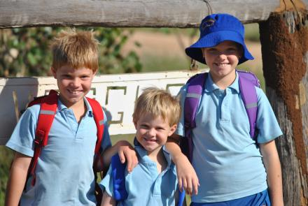 A picture of three school children wearing blue